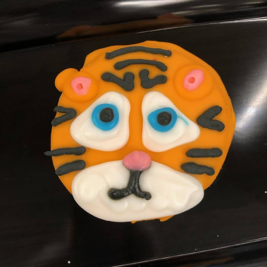 A frosted cookie decorated to look like a lion.