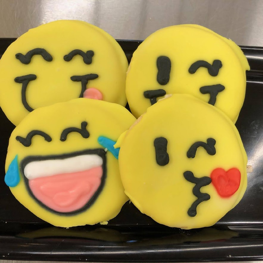 Four cookies frosted to look like emoji.