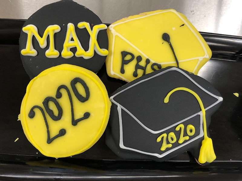 "Two cookies frosted to look like graduation caps and two others reading ""Max"" and ""2020"" in school colors."