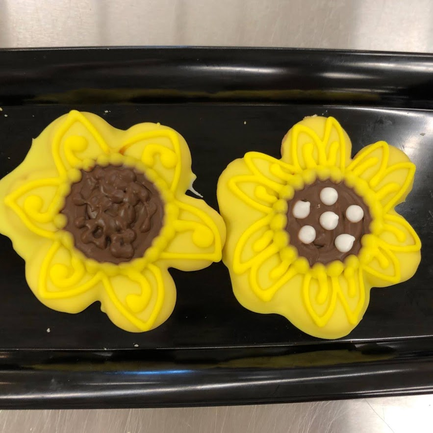 Two frosted cookies decorated to look like sunflowers.