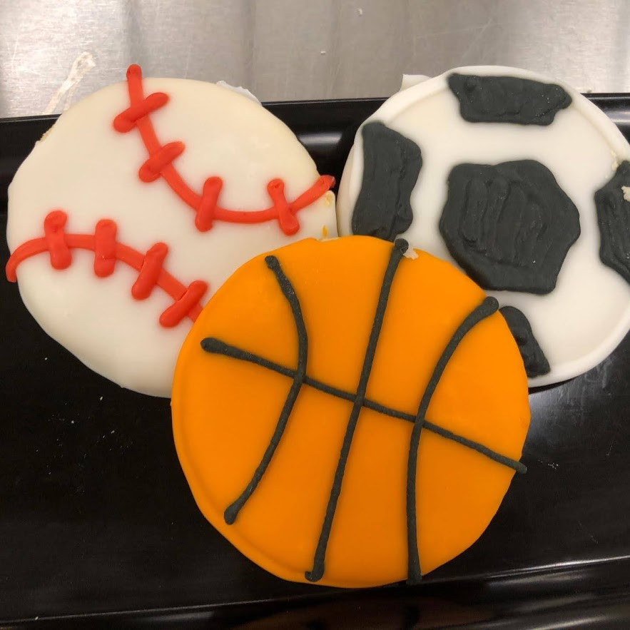 Three cookies frosted to look like a basketball, soccer ball and baseball.