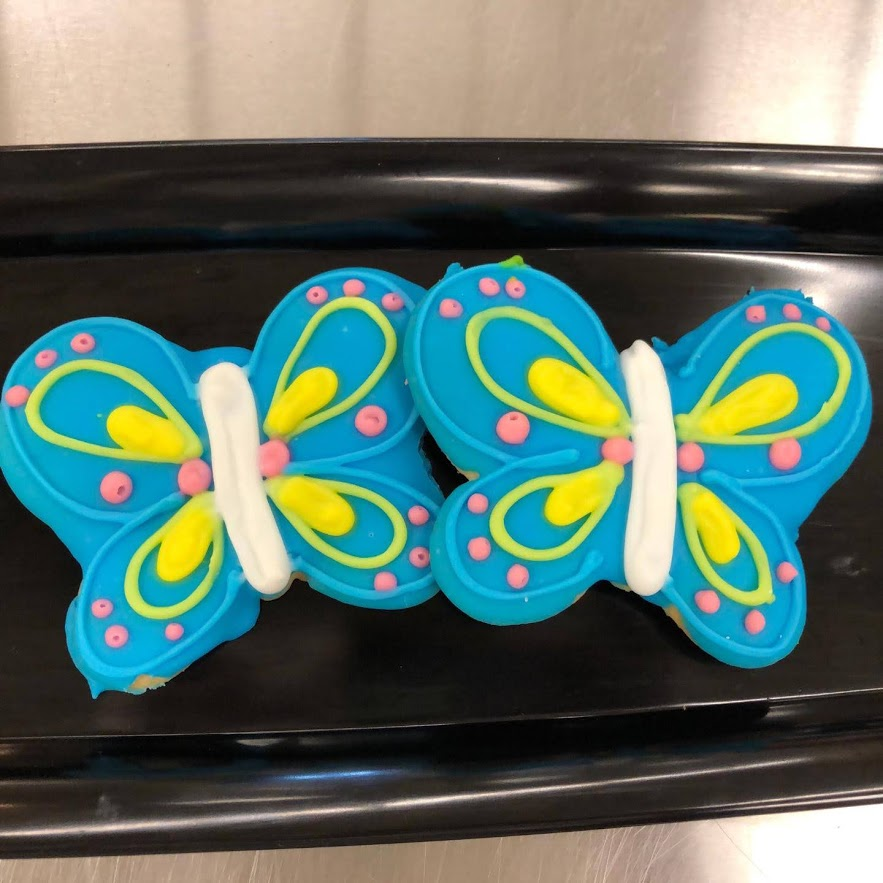 Two cookies frosted to look like butterflies.