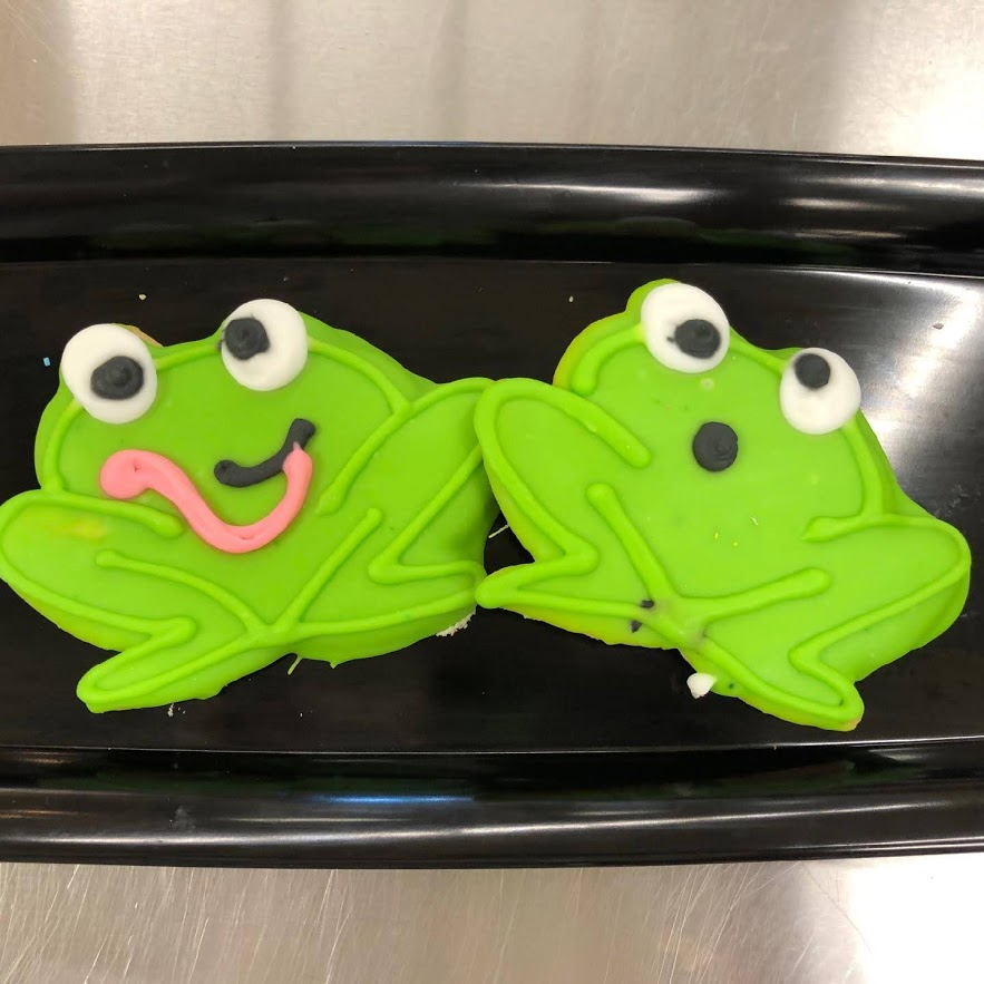 Two cookies frosted to look like frogs.