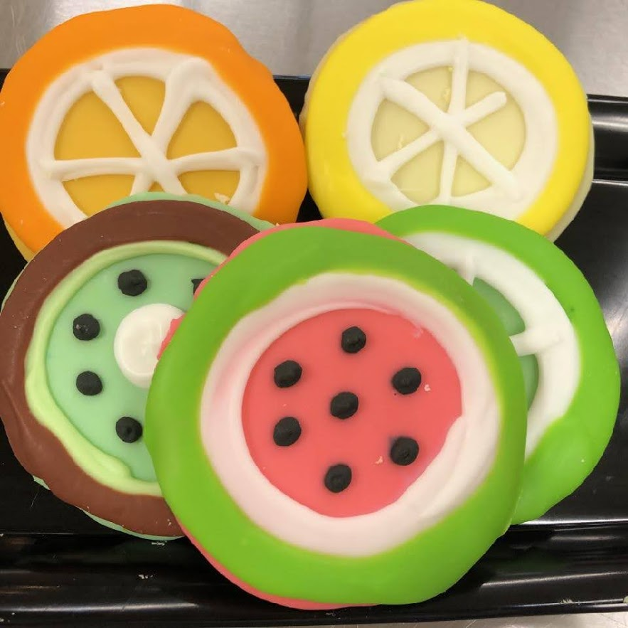Five cookies frosted to look like different citrus fruits.