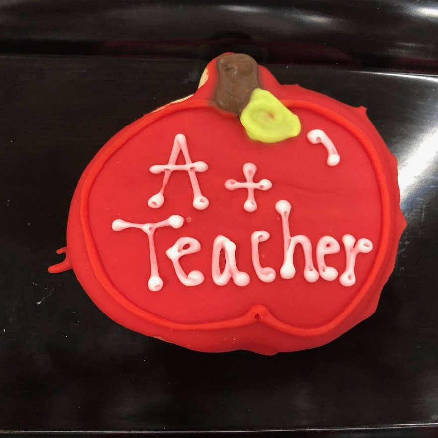"A cookie decorated to look like an apple that reads ""A+ Teacher""."