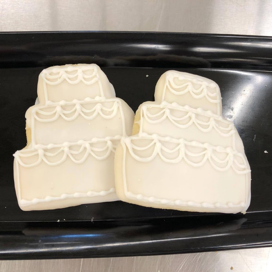 Two cookies frosted and shaped to look like wedding cakes.