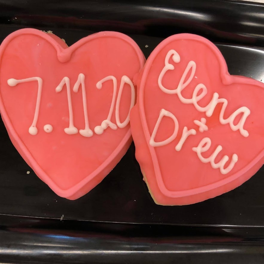 "Two heart shaped cookies frosted with red frosting and reading ""7.11.20"" and ""Elena + Drew"" in the center of each."