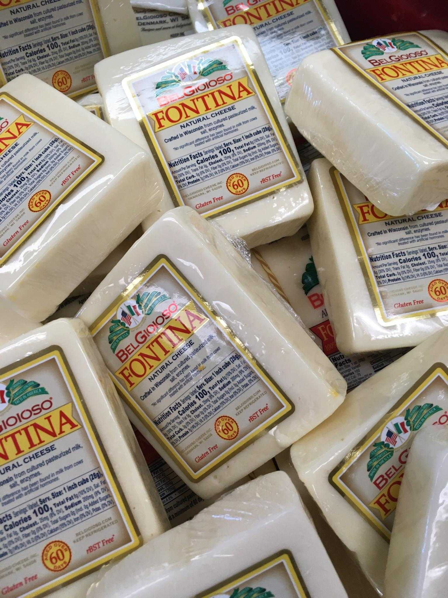 A pile of Belgioioso Fontina Cheese blocks.